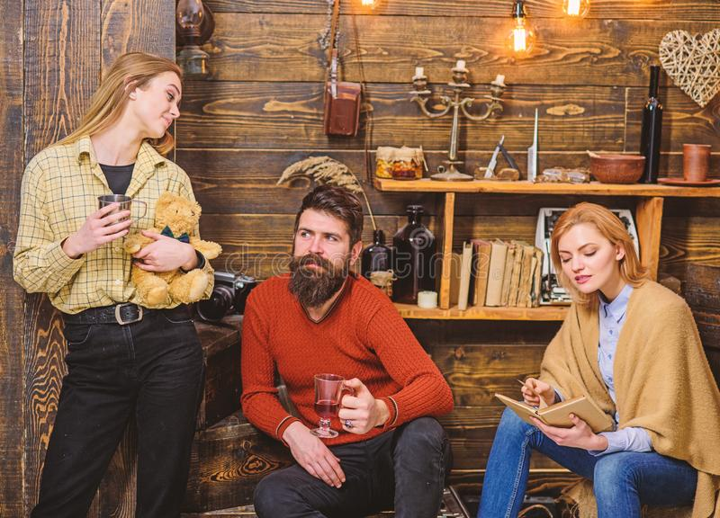 Woman absorbed by interesting book and not noticing her family. Girl with teddy bear in retro outfit standing next to. Wooden wall. Bearded men with cheerful royalty free stock photos