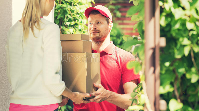 Woman accepting a home delivery of boxes from deliveryman stock image