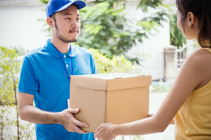 Woman accepting receive a delivery of boxes from delivery asian man. Sign and receive delivery concept focus on box royalty free stock photos