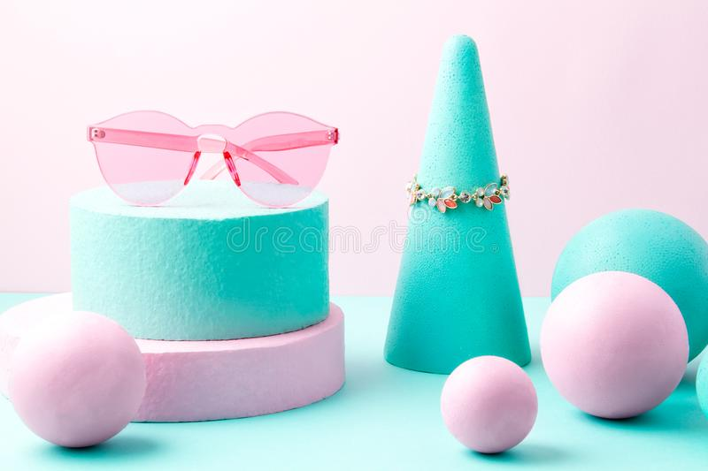 Woman accessories and geometric forms over the pink and turquoise background. Woman accessories and pastel geometric forms over the pink and turquoise background stock image