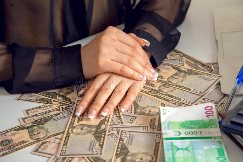 Woman accontant with a lot of money. Closeup of woman accountant hands and a lot of money on the table royalty free stock photo