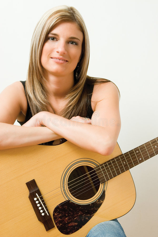 Woman with accoustic guitar. Thirty something woman sitting on stule leaning on accoustic guitar royalty free stock photo