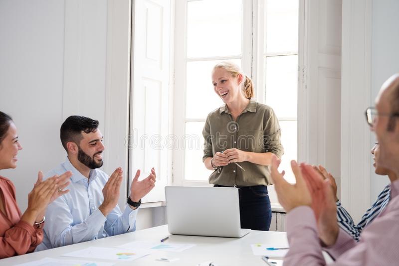 Woman acknowledging praise and applause at work. Woman acknowledging praise and applause from a group of motivated colleagues in an office setting after a body stock images