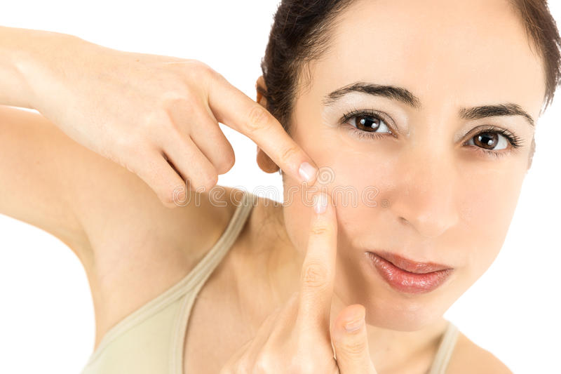 Woman with acne. Woman squeezing her acne spot. Isolated on white background royalty free stock photo