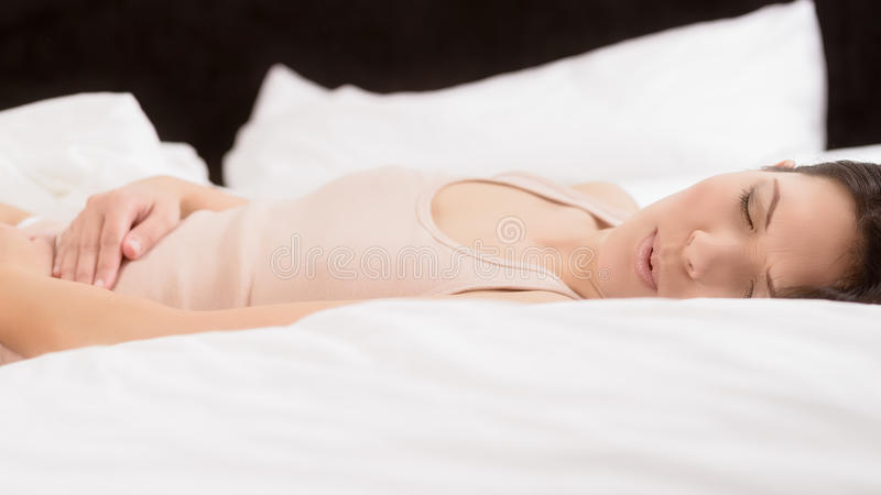 Woman with acute abdominal pain. Woman with her monthly menstrual pains clutching her stomach with her hands as she becomes stressed by the ongoing cramps while royalty free stock photo