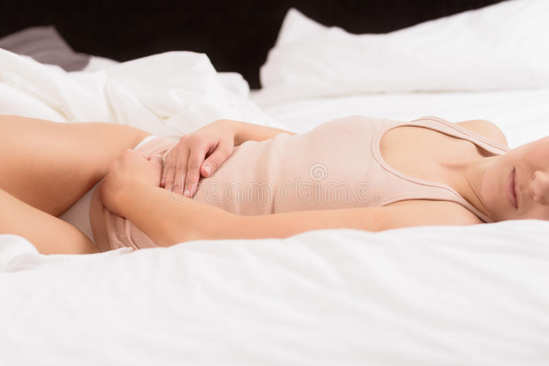 Woman with acute abdominal pain. Woman with her monthly menstrual pains clutching her stomach with her hands as she becomes stressed by the ongoing cramps while royalty free stock image