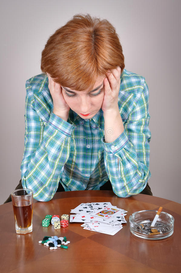 Woman addicted to vice. Depressed and sad woman sitting at the table and holding her head thinking about her addiction to alcohol, gambling and smoking stock photos
