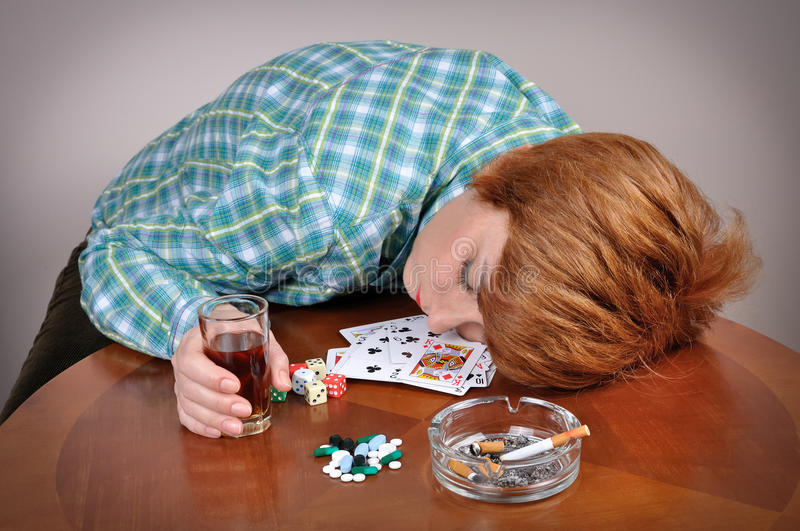 Woman addicted to vice. Exhausted woman with her head on the table sleeping next to cards, dice, pills and ashtray with cigarette holding a glass of alcohol royalty free stock image