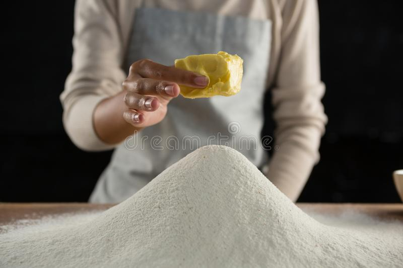 Woman adding butter cube into flour stock images