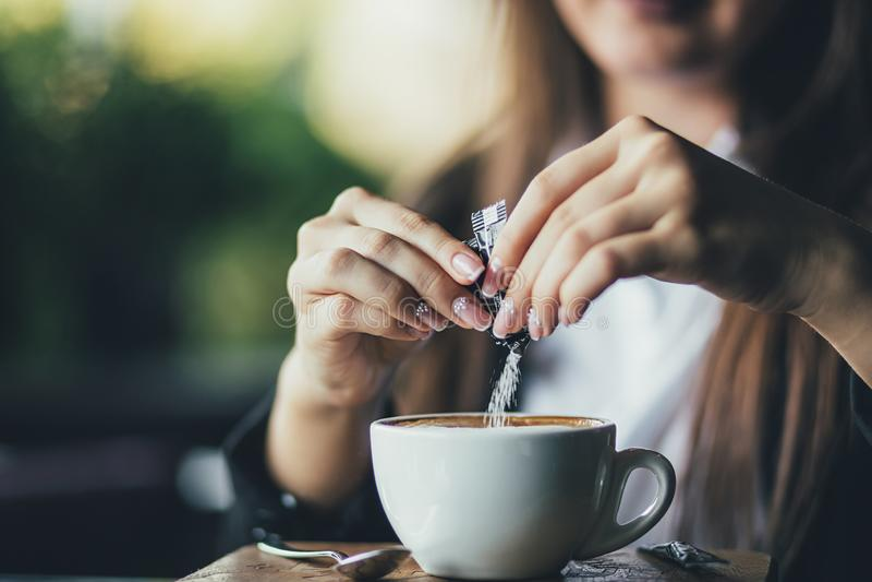 Woman adding sugar to fresh aromatic coffee on table, closeup.  stock image