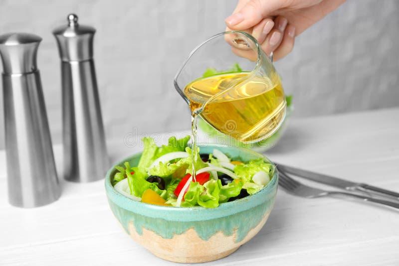 Woman adding tasty apple vinegar into salad stock images