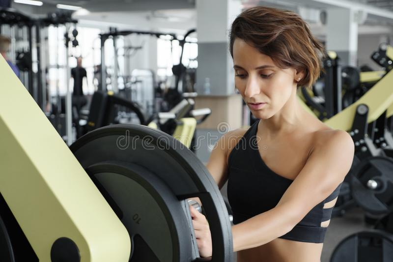 Woman adding weight on a bar as she workout in fitness gym royalty free stock photo