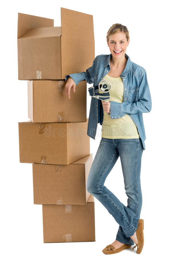 Woman With Adhesive Tape Leaning On Stacked Cardboard Boxes. Full length portrait of happy young woman with adhesive tape leaning on stacked cardboard boxes stock image