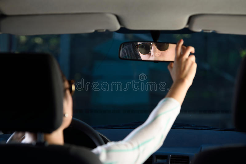Woman adjusting rear mirror royalty free stock photography