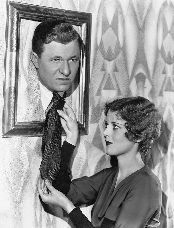 Woman adjusting tie of man in picture frame. (All persons depicted are no longer living and no estate exists. Supplier grants that there will be no model stock images
