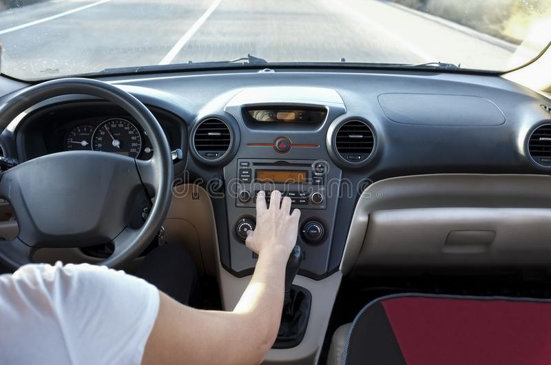 Woman adjusting volume at car audio system while she is driving. royalty free stock photo