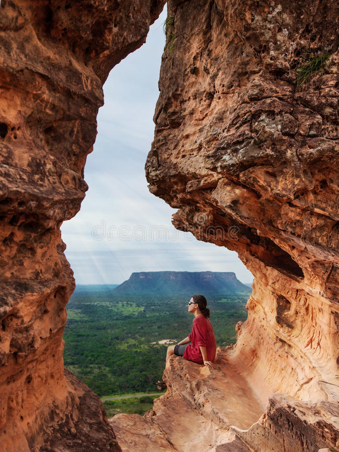 A woman admires the forest landscape sitting on a hole in a rock in Chapada das Mesas, Brazil. A young woman admires the rainy forest landscape sitting on a hole royalty free stock images