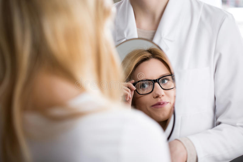 Woman admiring her reflection. Young pretty women in glasses admiring her reflection in mirror royalty free stock image