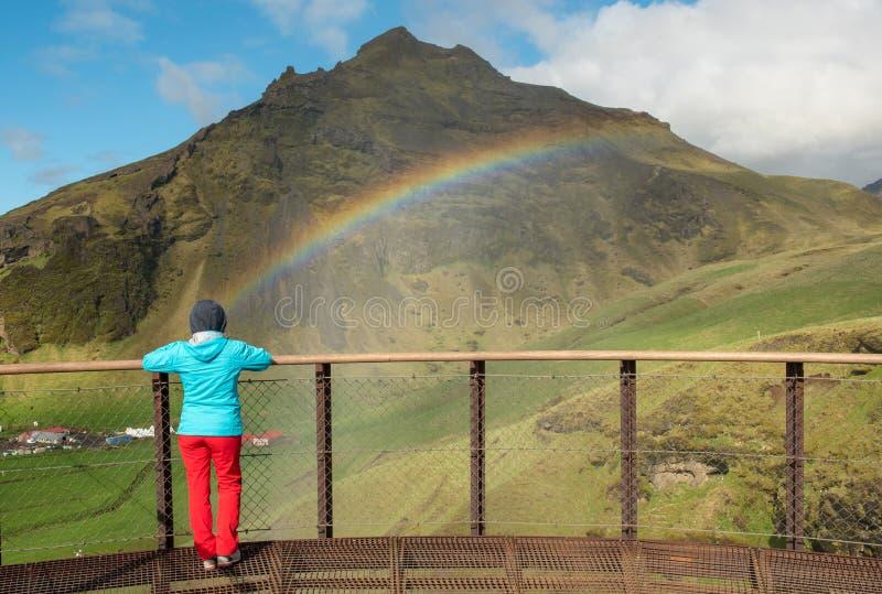 Woman admiring rainbow over the Skogafoss waterfall in Iceland stock photo