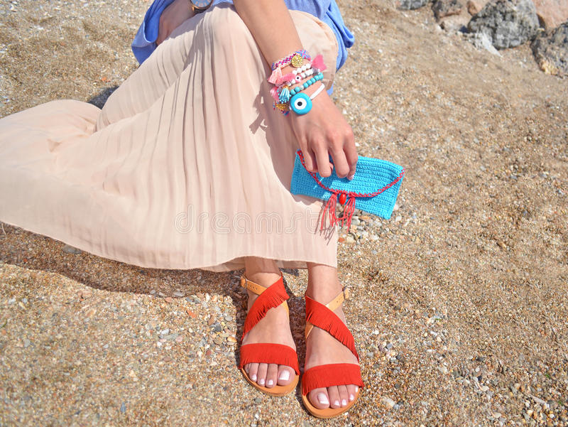 Woman advertises handmade accessories on beach. Greek sandals bag and jewelry royalty free stock photography