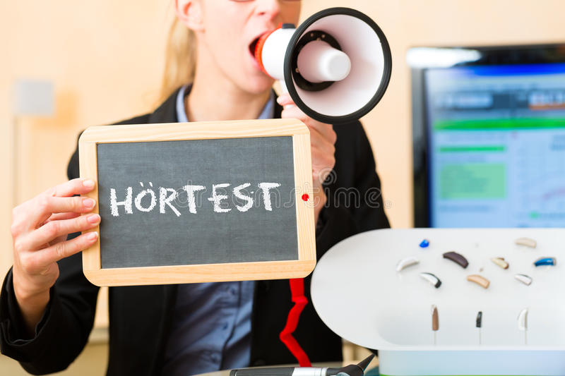 Woman advertising a hearing test. Young woman or acoustician holding a board or a board advertising a hearing test (in german language), besides her is a stock photo