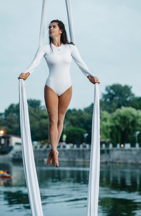 Woman aerialist performs acrobatic tricks on hanging aerial silk. Against background of river, sky and trees stock image