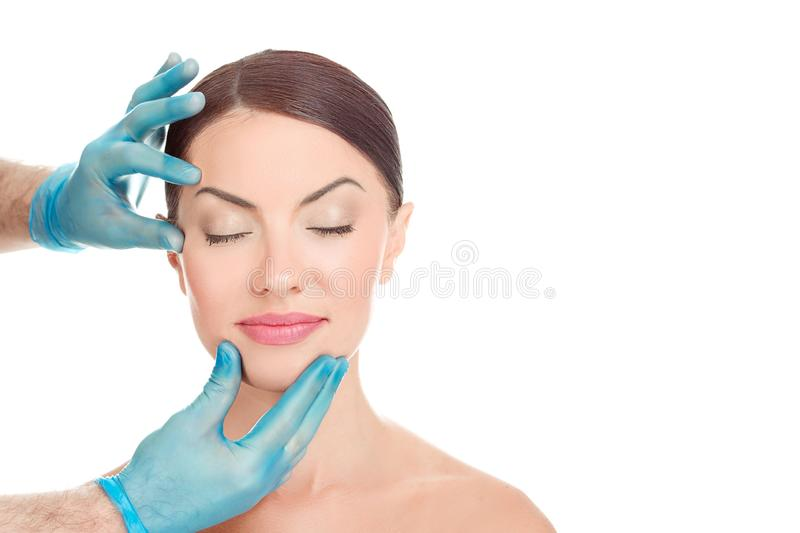 Woman after aesthetic surgery, while the doctor shows the results. White background. Woman with eyes closed after aesthetic surgery, smiles while the doctor stock photography