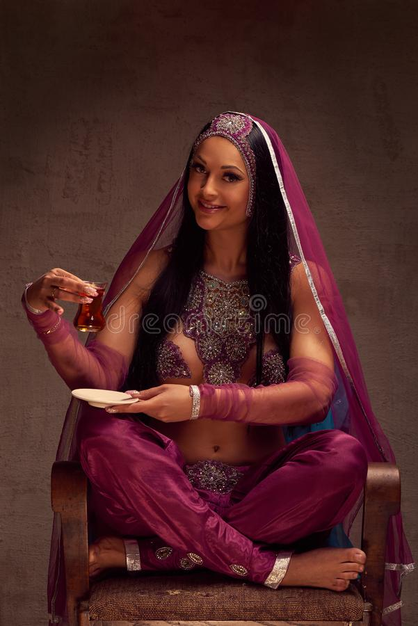 Woman in afghani pants, purdah and adornment have a tea armut royalty free stock photography