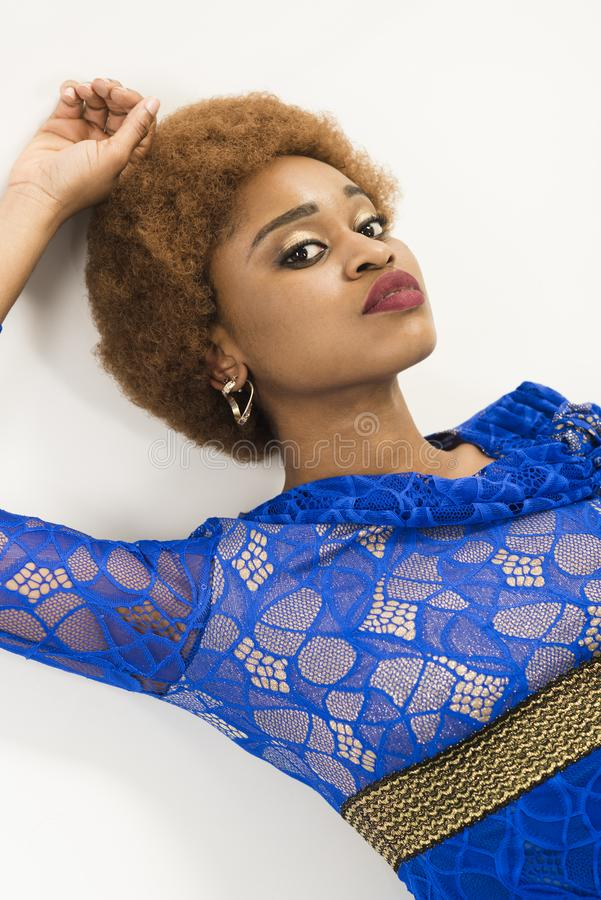 Woman with african appearance in blue dress looks gorgeous, white background. African females beauty concept. Lady on. Relaxed face with makeup and afro stock images