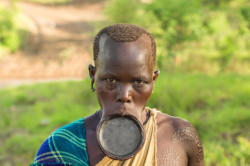 Woman from the african tribe surma with big lip plate for African body decoration