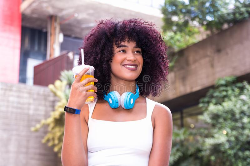 Woman with afro hairstyle with big smile. She is holding a cup of orange drink stock image