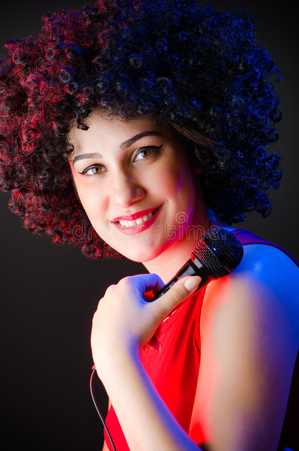 Woman with afro hairstyle singing in karaoke royalty free stock images