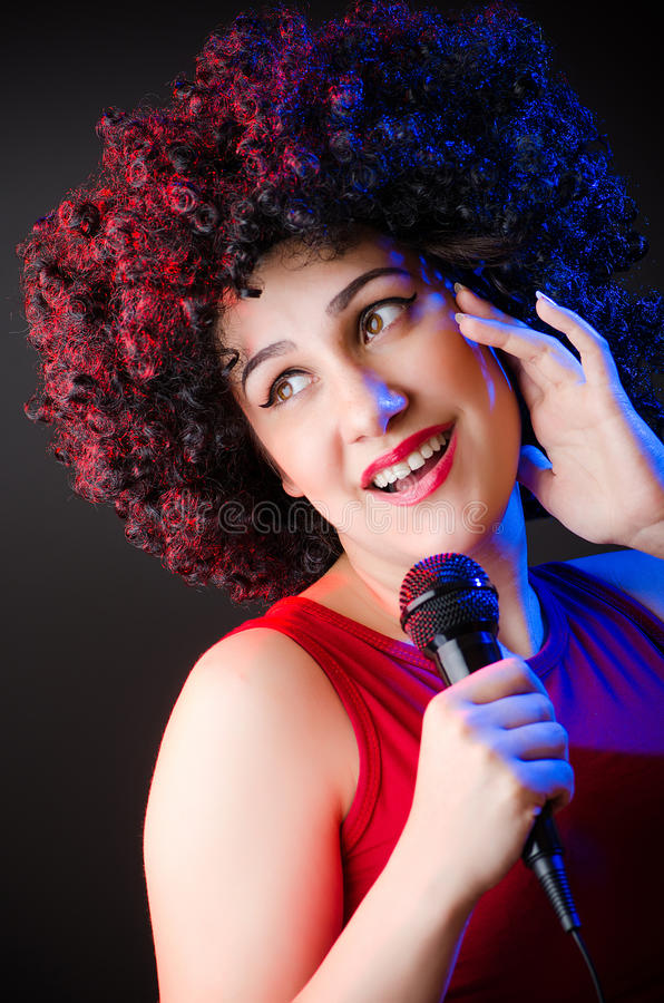 Woman with afro hairstyle singing in karaoke royalty free stock image