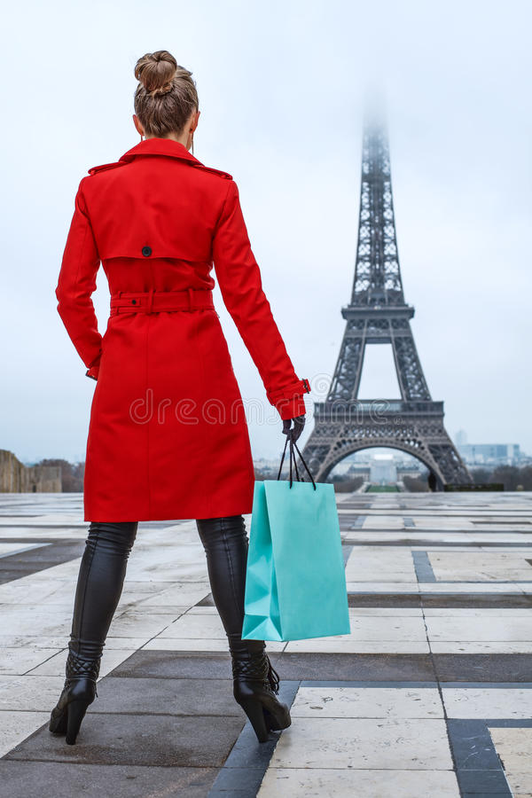 Woman against Eiffel tower in Paris, France with shopping bag. Bright in Paris. Seen from behind young woman in red trench coat against Eiffel tower in Paris royalty free stock image