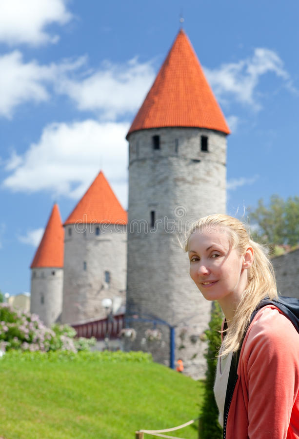 Woman against towers of a city wall in Tallinn. Estonia stock photography
