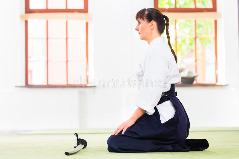 Woman at Aikido martial arts with sword. Woman sitting on mats while Aikido training in martial arts school royalty free stock photography