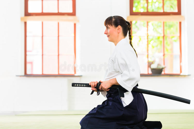 Woman at Aikido martial arts with sword. Woman sitting on mats while Aikido training in martial arts school stock photo