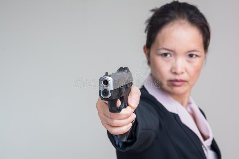 Woman aiming a hand gun stock photos