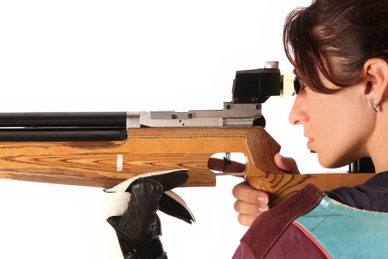 Woman aiming a pneumatic air rifle. Beautiful young woman aiming a pneumatic air rifle royalty free stock photos