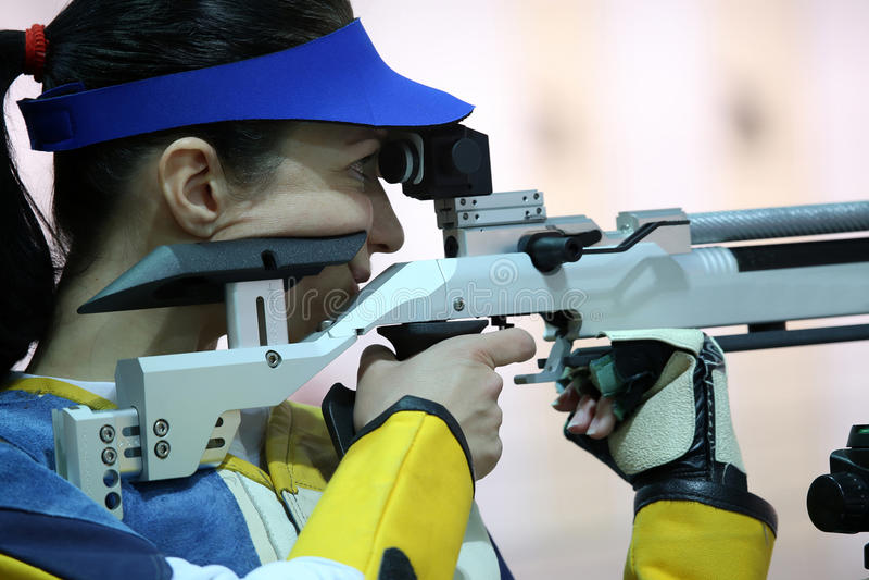 Woman aiming a pneumatic air rifle. Beautiful young woman aiming a pneumatic air rifle royalty free stock photography