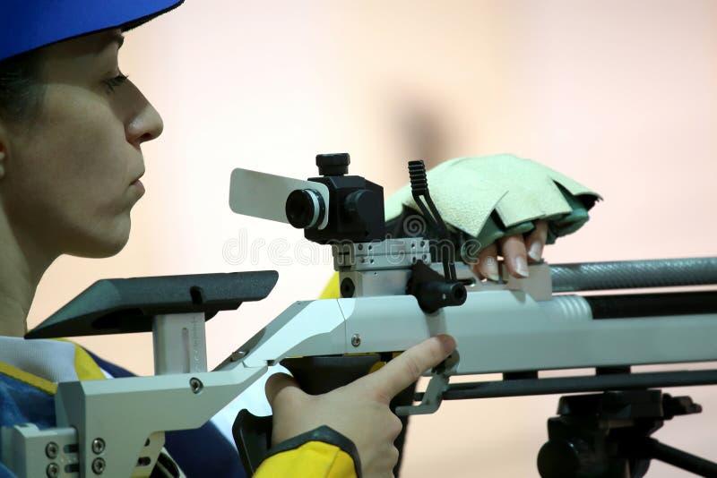 Woman aiming a pneumatic air rifle. Beautiful young woman aiming a pneumatic air rifle stock photos