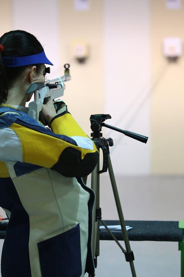Woman aiming a pneumatic air rifle. Beautiful young woman aiming a pneumatic air rifle royalty free stock photo