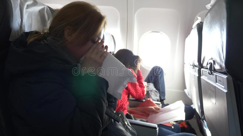 Woman in an airplane with children on a porthole background. the plane entered the zone of turbulence. the girl started. Panicking, she breathes into a paper stock photos