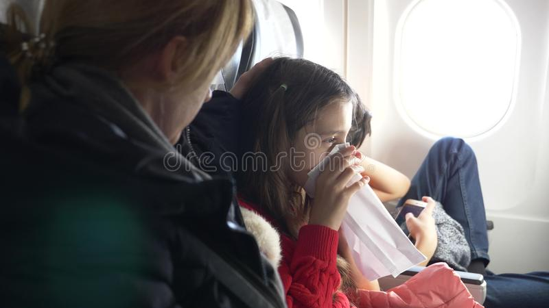 Woman in an airplane with children on a porthole background. the plane entered the zone of turbulence. the girl started. Panicking, she breathes into a paper stock images