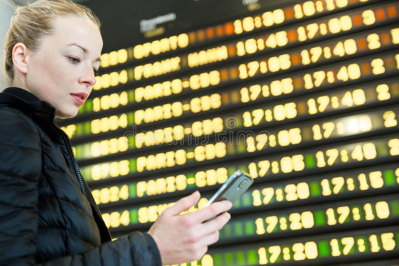 Woman at airport in front of flight information board checking her phone. stock images