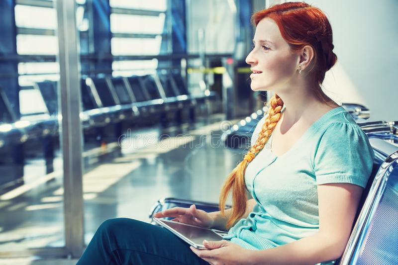 Woman at an airport waiting room. girl with tablet computer royalty free stock photos