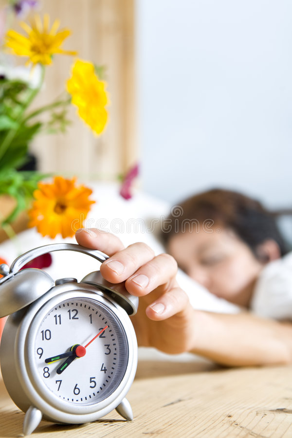 Woman and alarm. Close up view of table clock and woman sleeping on back stock photography