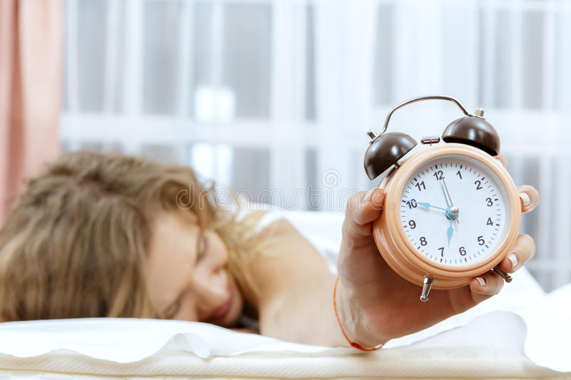 Woman with alarmclock on the bed. stock photos