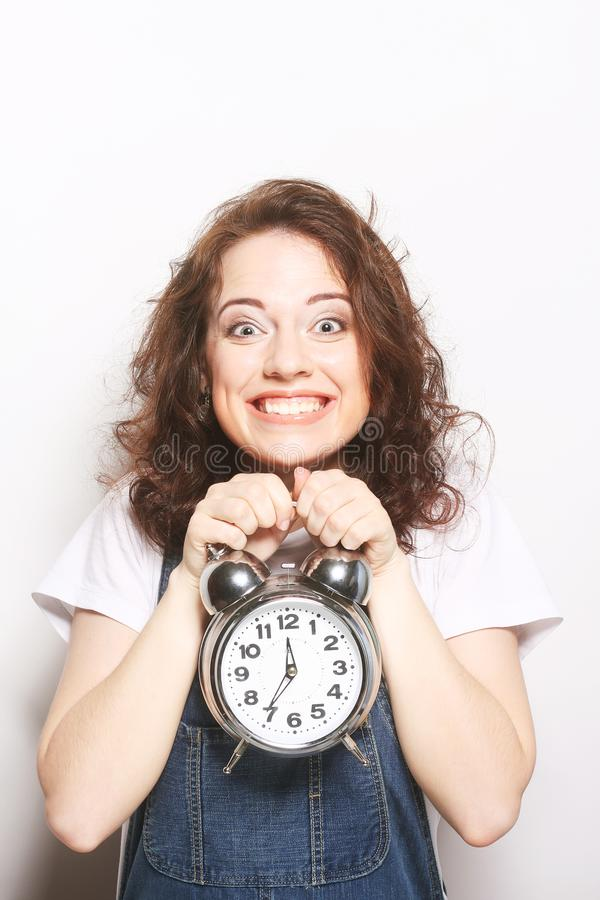 Woman with alarmclock. Young fun woman with alarmclock royalty free stock images
