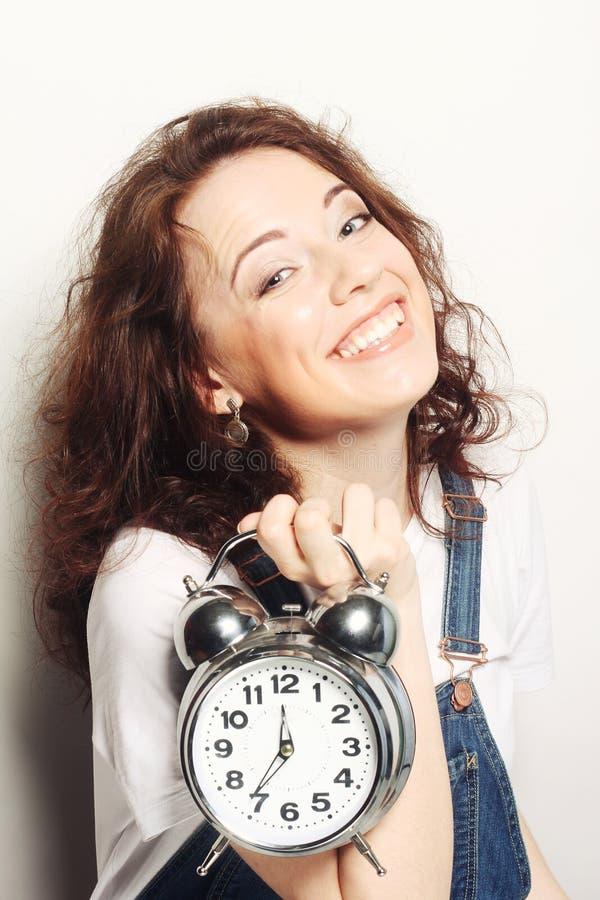 Woman with alarmclock. Young fun woman with alarmclock stock images